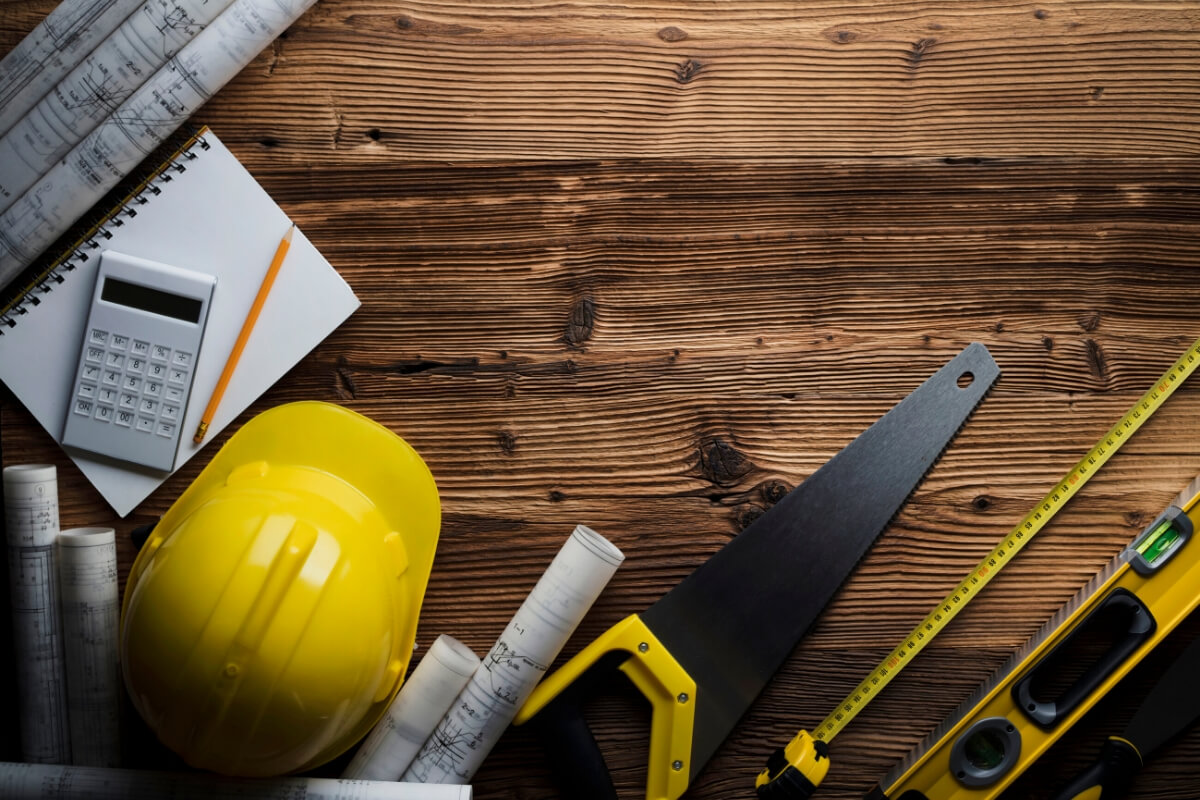 tools and blueprints on wood background